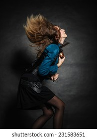 music love passion concept. Young woman with flying long hair dancing. Studio shot on grunge background