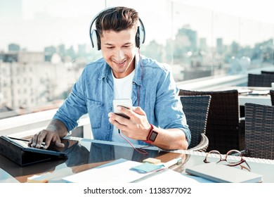 Music lover. Cheerful male person bowing head and smiling while choosing necessary song