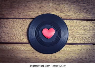 Music Lover - Vinyl with red love heart on a wooden surface