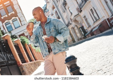 Music lover. Young guy wearing earphones sitting on city street listening to music holding cup drinking coffee smiling joyful