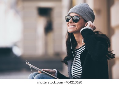 Music makes her day. Side view of beautiful young woman in sunglasses adjusting her headphones and looking away with smile while sitting outdoors