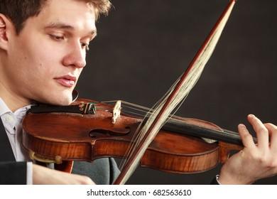 Music, misfortune, bad luck concept. Young man violinist dressed elegantly shocked, broken bow. Studio shot on dark background