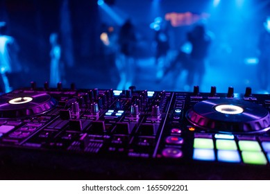music mixer DJ controller in booth at nightclub party