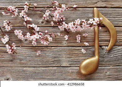 Music note with blossom branch pink flowers on wooden background