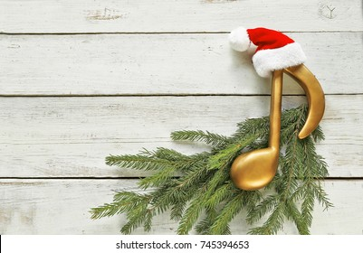 Music note with santa hat  on christmas tree branch on wooden