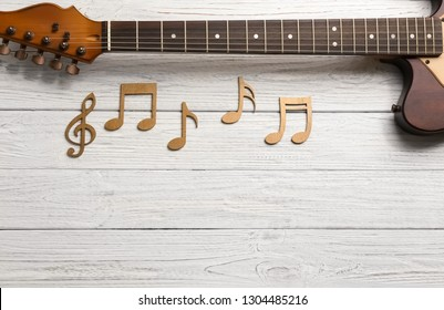 Music notes and guitar neck on wooden background, top view. Space for text