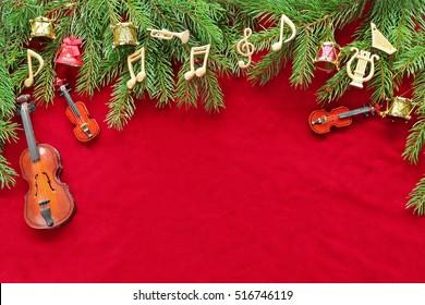Music notes, instruments on christmas tree on red velvet