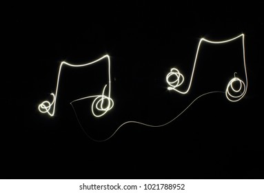 Music notes on black background created by using freeze light effect.
