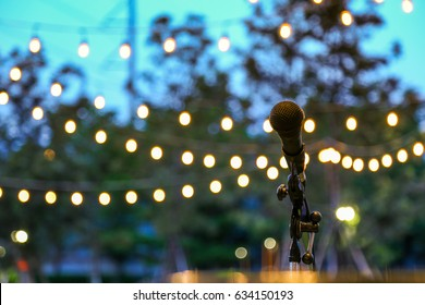 Music in the park, microphone on stand with hanging light background in the evening