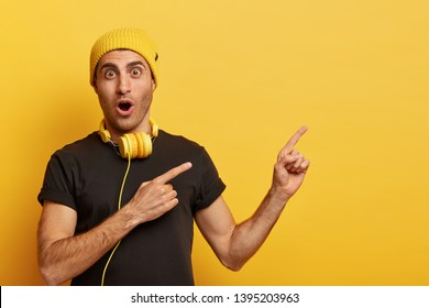 Music is part of technology. Surprised Caucasian man wears headphones, yellow headgear and black t shirt, astonished by something, points aside with two fore fingers, isolated on yellow background