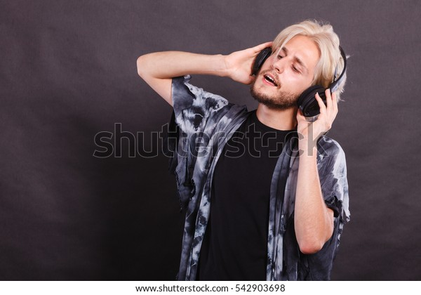 Music, pasion, male artist concept. Blonde man singing in studio wearing big black headphones. Indoor shot on dark grunge background