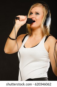 Music, passion concept. Studio shot of blonde young woman singing to microphone and wearing big headphones on her head performing songs and having fun