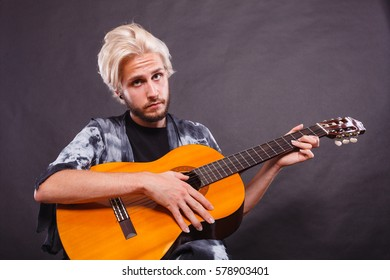 Music, passion concept. Young blonde man wearing fancy shirt playing on acoustic guitar, studio shot, black background.