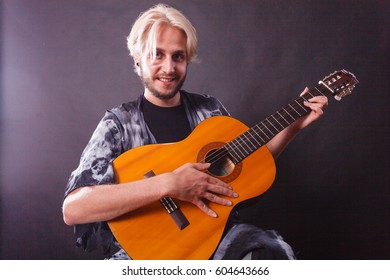 Music, passion concept. Young blonde man smiling wearing fancy shirt playing on acoustic guitar, studio shot, black background.