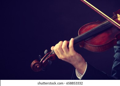 Music passion, hobby concept. Close up young man man dressed elegantly playing on wooden violin. Studio shot on dark background