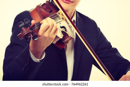 Music passion, hobby concept. Close up young man man dressed elegantly playing on wooden violin. Studio shot on white background