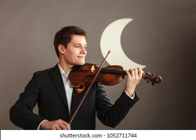 Music passion, hobby concept. Young man man dressed elegantly playing on wooden violin. Studio shot on dark background with white moon