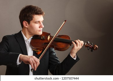 Music passion, hobby concept. Young man man dressed elegantly playing on wooden violin. Studio shot on dark background