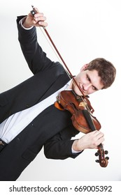 Music passion, hobby concept. Young man man dressed elegantly playing on wooden violin. Studio shot on white background