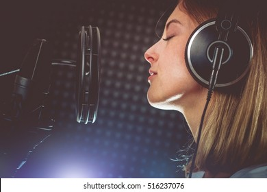 Music Passionate Singer and the Microphone. Young Caucasian Singer in Her 20s Recording Album in the Professional Studio. Singing with Passion.
