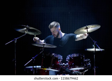 music, people, musical instruments and entertainment concept - male musician with drumsticks playing drums and cymbals at concert or studio