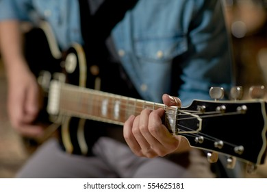 music, people, musical instruments and entertainment concept - close up of male guitarist playing electric guitar at studio rehearsal