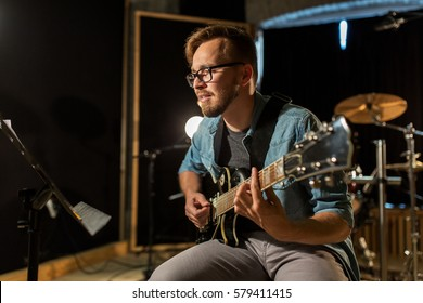 music, people, musical instruments and entertainment concept - male guitarist playing electric guitar with stand at studio rehearsal