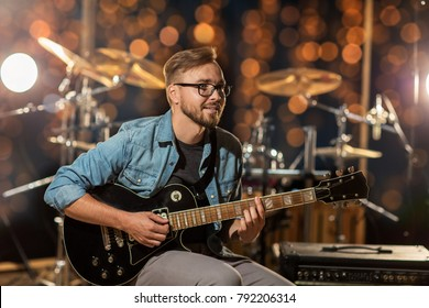 music, people, musical instruments and entertainment concept - male guitarist playing electric guitar at studio rehearsal over holidays lights background