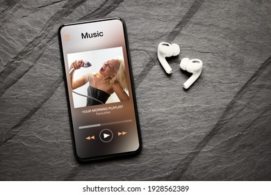 Music player on screen of mobile phone and wireless earphones on dark background