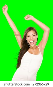 Music player woman dancing with earphones. Girl happy and joyful listening to music wearing earphones. Portrait of cheerful Chinese Asian / Caucasian female model isolated cutout on green background.