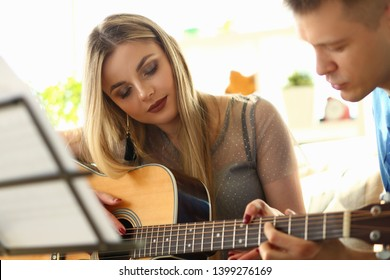 Music Playing Lesson Lovers Couple at Living Room. Caucasian Beautiful People with Acoustic Guitar. Girl Touching Strings, Learning Chords. Professional Performer have Fun Teaching