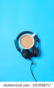 Music or podcast background with headphones and cup of coffee on blue table, flat lay. Top view, flat lay