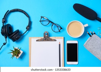 Music or podcast background with headphones, microphone, coffee and blank on blue table, flat lay. Top view, flat lay