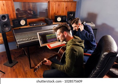 Music producer and artist with acoustic guitar together in music studio , sitting in front of mixing desk