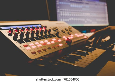 music producer hands playing midi keyboard synthesizer in recording studio, shallow dept of field. focus on knob