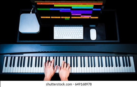 music production technology, male composer hands working on piano keys with computer on desk