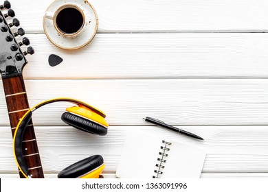 Music record studio with guitar, coffee, headphones and notebook white wooden background top view copyspace
