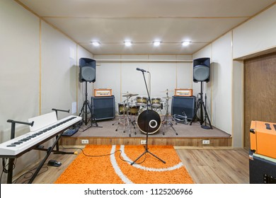 Music rehearsal space with drum kit and musical equipment.