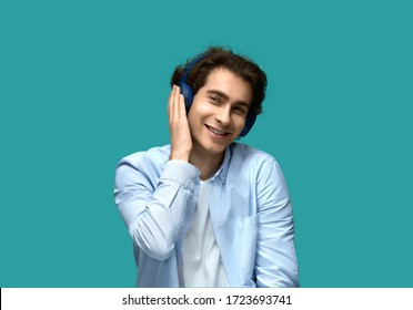 Music relaxation. Portrait of a young beautiful man wearing white t-shirt and blue shirt in headphones covers ear with hand smiles from enjoying sounds