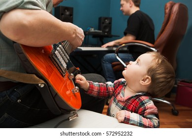 Music rock Band Rehearsal Friendship Together. the baby on a father's musical repetion. The man plays the electro guitar, and his friend on a synthesizer.