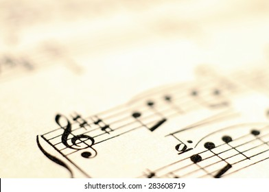 Music score background, piano notes on old paper, close up