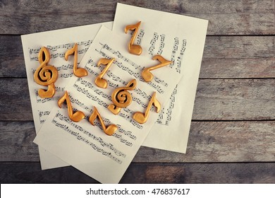 Music sheets with golden notes on wooden background