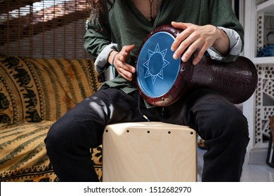 Music shot of a white man playing cajon drum box and arabic darbuka at the same time on an alternative house studio background. Having fun experimenting with exotic instruments at home.