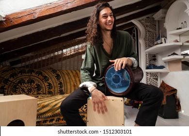 Music shot of a young handsome man playing cajon drum box and arabic darbuka at the same time on an alternative house studio background. Having fun experimenting with exotic instruments at home.