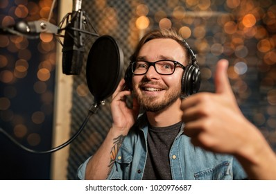 music, show business, people and voice concept - male singer with headphones and microphone singing song at sound recording studio and showing thumbs up over festive lights