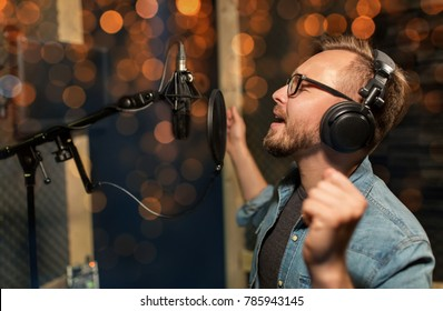 music, show business, people and voice concept - male singer with headphones and microphone singing song at sound recording studio over holidays lights background