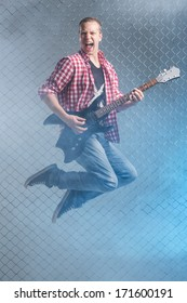 Music, sound. Musician with a guitar on fence background