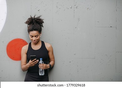 Music and sport. Smiling muscular african american young woman with headphones, smart watch and bottle of water looks at smartphone on wall background, free space