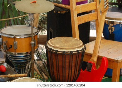 A music stage with lots of instruments and a wooden chair outdoors.