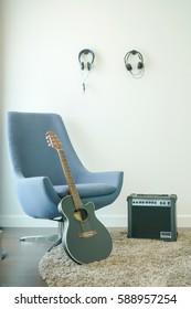 Music studio with gray armchair, guitar and headphones